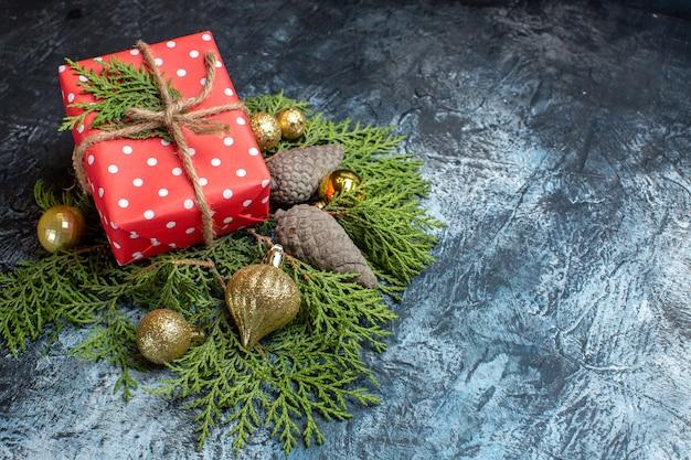 Vista frontal de regalo de navidad con rama verde y juguetes en superficie ligera
