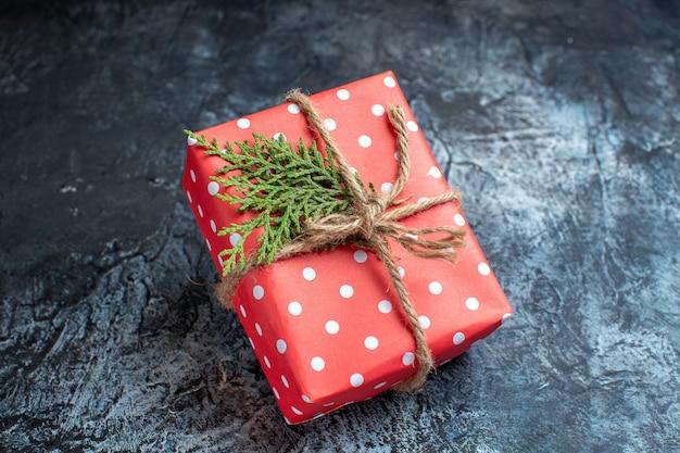 Vista frontal del regalo de navidad en la superficie de la luz