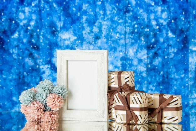 Vista frontal regalos del día de san valentín flores marco de fotos blanco reflejado en el espejo en el espacio de copia de fondo de acuarela azul