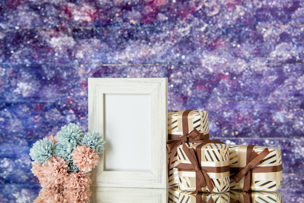 Vista frontal regalos del día de san valentín flores marco de fotos blanco reflejado en el espejo sobre fondo de acuarela púrpura espacio libre