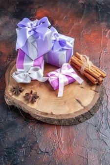 Vista frontal regalos de navidad anís canela sobre tabla de cortar árboles sobre fondo rojo oscuro