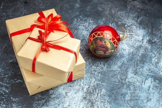 Vista frontal de regalos de navidad atados con lazos rojos en el color claro-oscuro regalo de navidad de año nuevo
