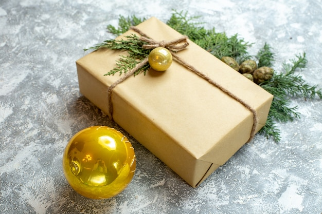 Vista frontal de regalos de navidad con rama verde y juguetes sobre fondo blanco.