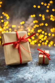 Vista frontal de regalos navideños con luces amarillas en color de año nuevo navideño claro-oscuro