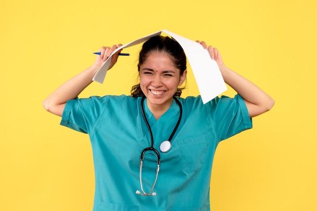 Vista frontal regocijado doctora con documentos sobre fondo amarillo