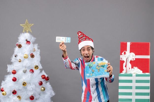 Vista frontal regocijado hombre sosteniendo mapa y boleto de viaje