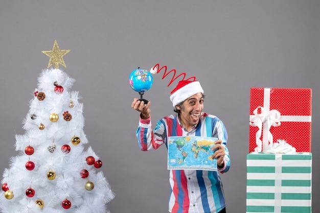 Vista frontal regocijado hombre sosteniendo mapa del mundo y globo cerca del árbol de navidad y regalos