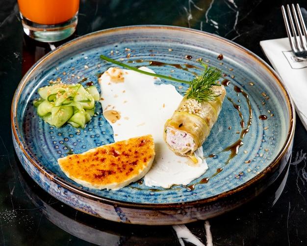 Vista frontal rellena de calabacín con una rodaja de queso y pepino en un plato azul