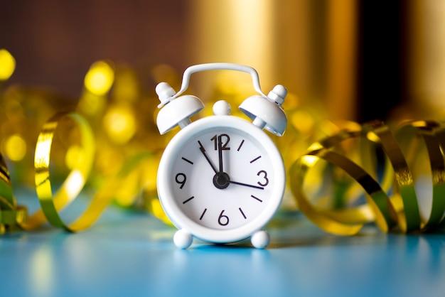 Vista frontal del reloj blanco sobre fondo dorado de cinta