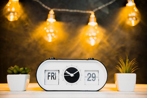 Vista frontal del reloj y bombillas con mesa de madera
