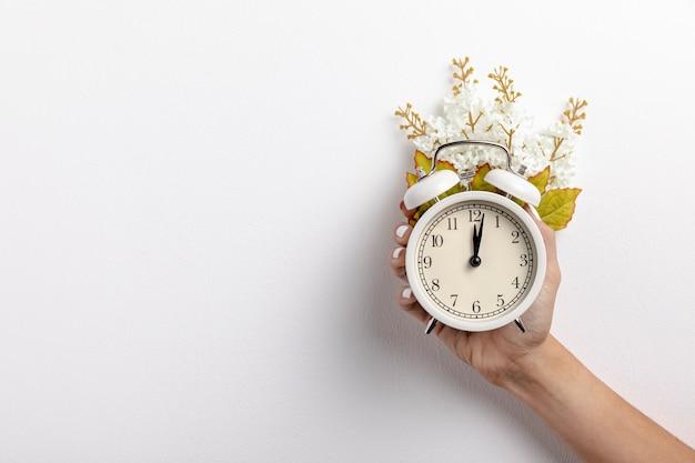 Vista frontal del reloj en la mano con hojas y flores.