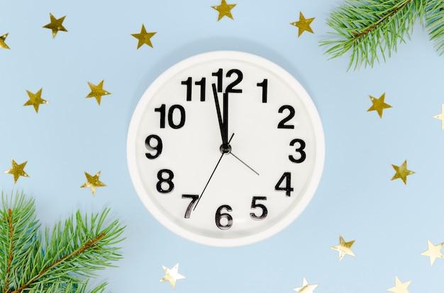Vista frontal del reloj de medianoche con estrellas doradas y hojas de pino