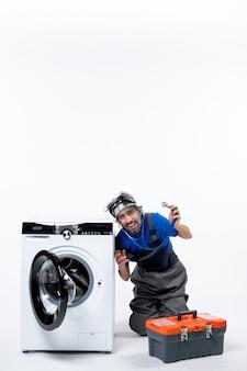Vista frontal reparador alegre sosteniendo estetoscopio sentado cerca de la lavadora en el espacio en blanco