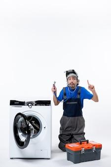 Vista frontal reparador interesado sosteniendo estetoscopio sentado cerca de la lavadora en el espacio en blanco