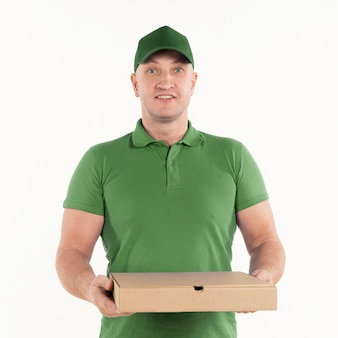 Vista frontal del repartidor con caja de pizza y sonriendo