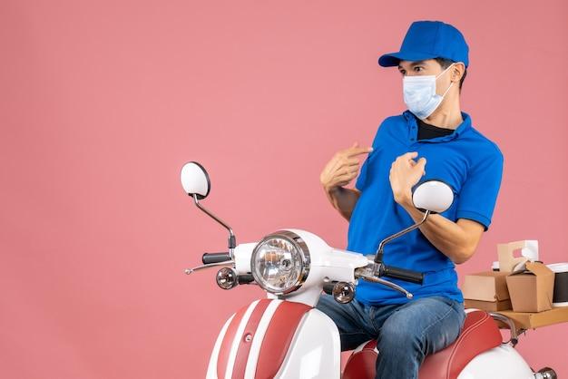 Vista frontal del repartidor confundido con máscara médica con sombrero sentado en scooter sobre fondo de melocotón pastel
