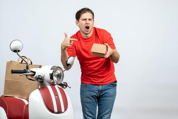 Vista frontal del repartidor confundido en uniforme rojo de pie cerca de scooter apuntando una pequeña caja sobre fondo blanco.
