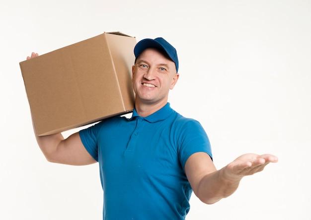 Vista frontal del repartidor llevando una caja de cartón