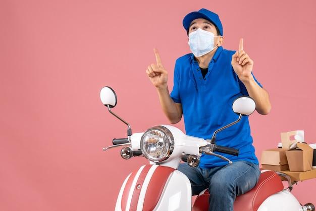 Vista frontal del repartidor con máscara médica con sombrero sentado en scooter y apuntando hacia arriba sobre fondo melocotón pastel