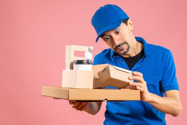 Vista frontal del repartidor masculino sorprendido con sombrero mostrando pedidos
