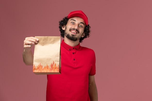 Vista frontal repartidor de mensajería masculino en camisa roja y capa con paquete de comida de papel en la pared rosa empleado de la empresa de entrega de servicios de trabajo