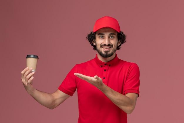 Vista frontal repartidor de mensajería masculino en camisa roja y capa sosteniendo una taza de café marrón en la pared de color rosa claro trabajador empleado de entrega uniforme de servicio
