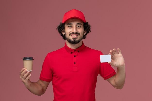 Vista frontal repartidor de mensajería masculino en camisa roja y capa sosteniendo una taza de café marrón con tarjeta en la pared rosa claro empleado de servicio de entrega uniforme