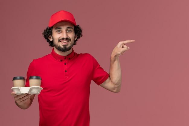 Vista frontal repartidor de mensajería masculino en camisa roja y capa sosteniendo tazas de café de entrega marrón en la pared rosa empleado trabajador de entrega de servicio