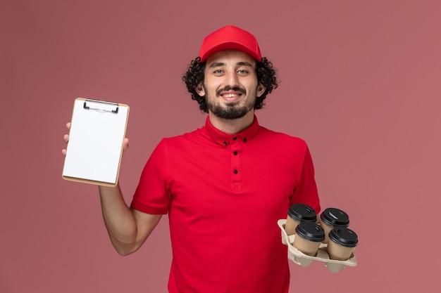 Vista frontal repartidor de mensajería masculino en camisa roja y capa sosteniendo tazas de café de entrega marrón con un pequeño bloc de notas en la pared rosa empleado de servicio de entrega