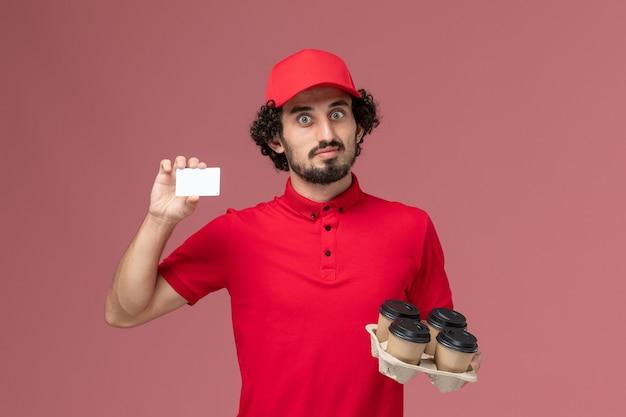 Vista frontal repartidor de mensajería masculino en camisa roja y capa sosteniendo tazas de café de entrega marrón con tarjeta de plástico en el trabajo de empleado de entrega de servicio de pared rosa