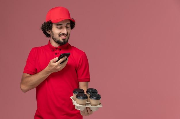 Vista frontal repartidor de mensajería masculino en camisa roja y capa sosteniendo tazas de café de entrega marrón y tomando una foto en la pared rosa claro empleado de servicio de entrega