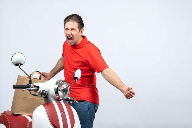 Vista frontal del repartidor nervioso emocional en uniforme rojo de pie cerca de scooter sobre fondo blanco.