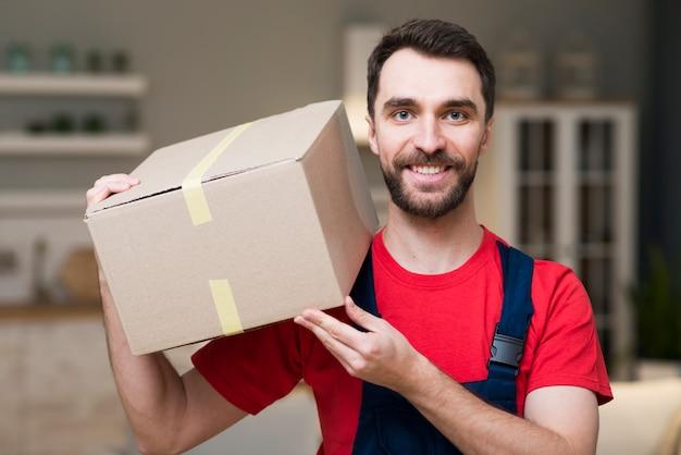 Vista frontal del repartidor posando con cajas