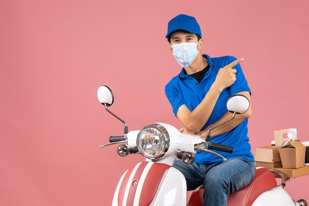 Vista frontal del repartidor preguntándose en máscara médica con sombrero sentado en scooter sobre fondo de melocotón pastel