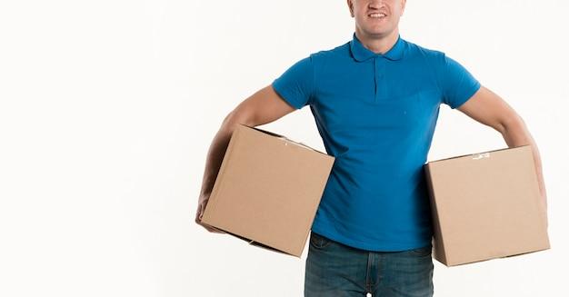 Vista frontal del repartidor sonriente con cajas de cartón