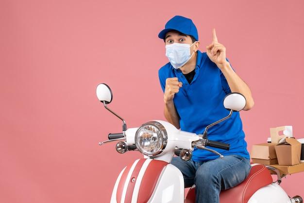 Vista frontal del repartidor sorprendido en máscara médica con sombrero sentado en scooter y apuntando hacia arriba sobre fondo de melocotón pastel