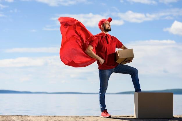 Vista frontal repartidor vistiendo capa de superhéroe