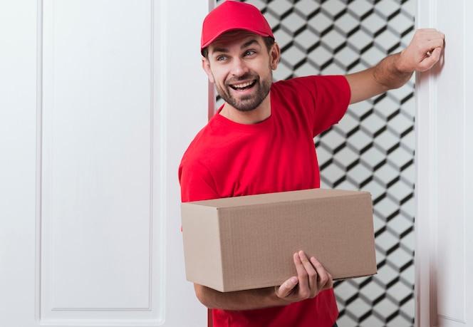 Vista frontal repartidor vistiendo uniforme rojo y llamando a la puerta