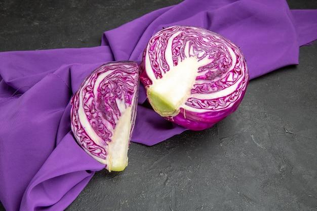 Vista frontal de repollo rojo en rodajas de verduras en la dieta de salud de ensalada de mesa oscura