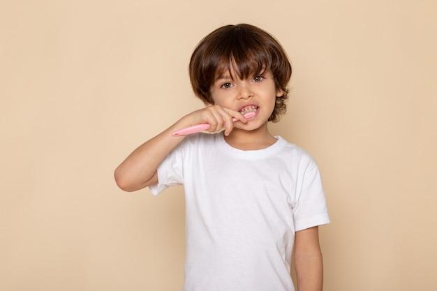 Vista frontal del retrato, chico lindo adorable en camiseta blanca sobre escritorio rosa