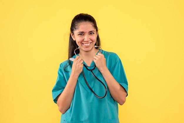 Vista frontal riendo doctora sosteniendo estetoscopio en sus manos de pie sobre fondo amarillo