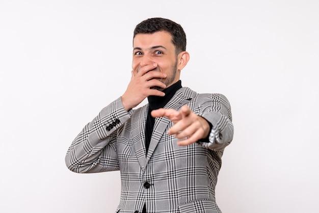 Vista frontal riendo hombre guapo en traje de pie sobre fondo blanco.