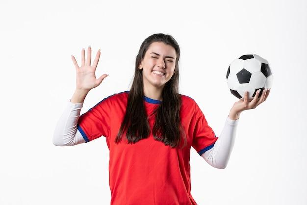 Vista frontal riendo a mujeres jóvenes en ropa deportiva con balón de fútbol