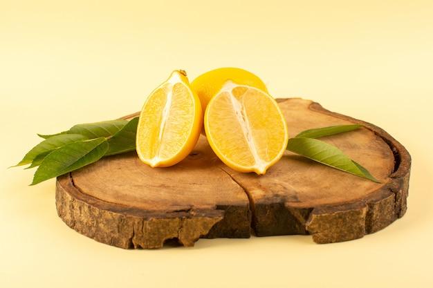 Una vista frontal en rodajas de limón y todo con hojas verdes en el escritorio de madera marrón aislado fresco y jugoso suave en la crema