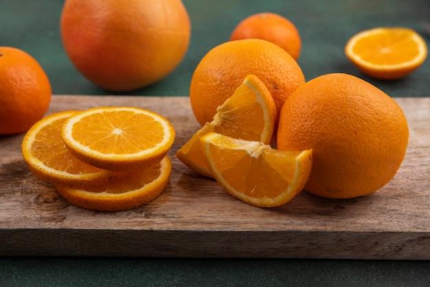 Vista frontal de rodajas de naranja en la tabla de cortar sobre fondo verde