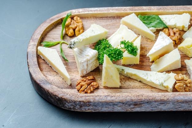 Vista frontal en rodajas de queso roquefort con verduras y nueces en un plato de madera
