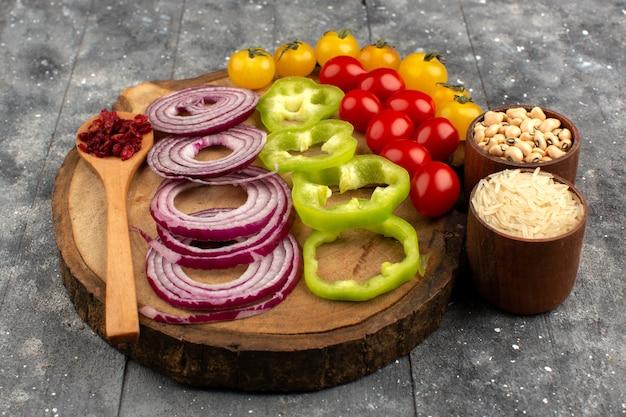 Vista frontal rodajas de verduras como cebollas pimientos verdes tomates amarillos y rojos en el escritorio marrón y gris