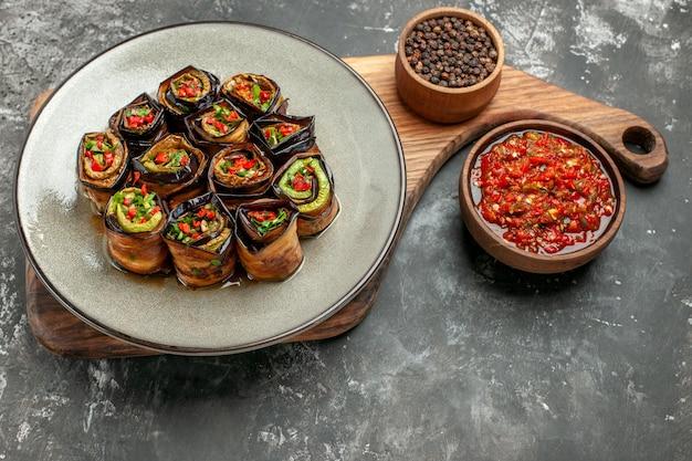 Vista frontal rollos de berenjena rellenos en plato ovalado blanco pimienta negra en un tazón sobre tabla de servir de madera con mango adjika sobre fondo gris