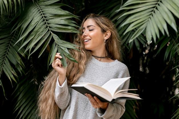 Vista frontal rubia mujer sosteniendo un libro abierto