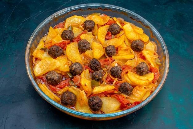 Vista frontal sabrosa comida de patata con albóndigas y tomates sobre fondo azul oscuro.